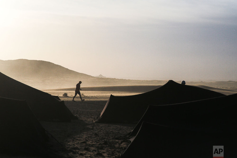 A competitor walks during sunrise in the bivouac before the start of a new stage in the 33rd edition of Marathon des Sables, in the Sahara desert, near Merzouga, southern Morocco, Friday, April 13, 2018. (AP Photo/Mosa'ab Elshamy)