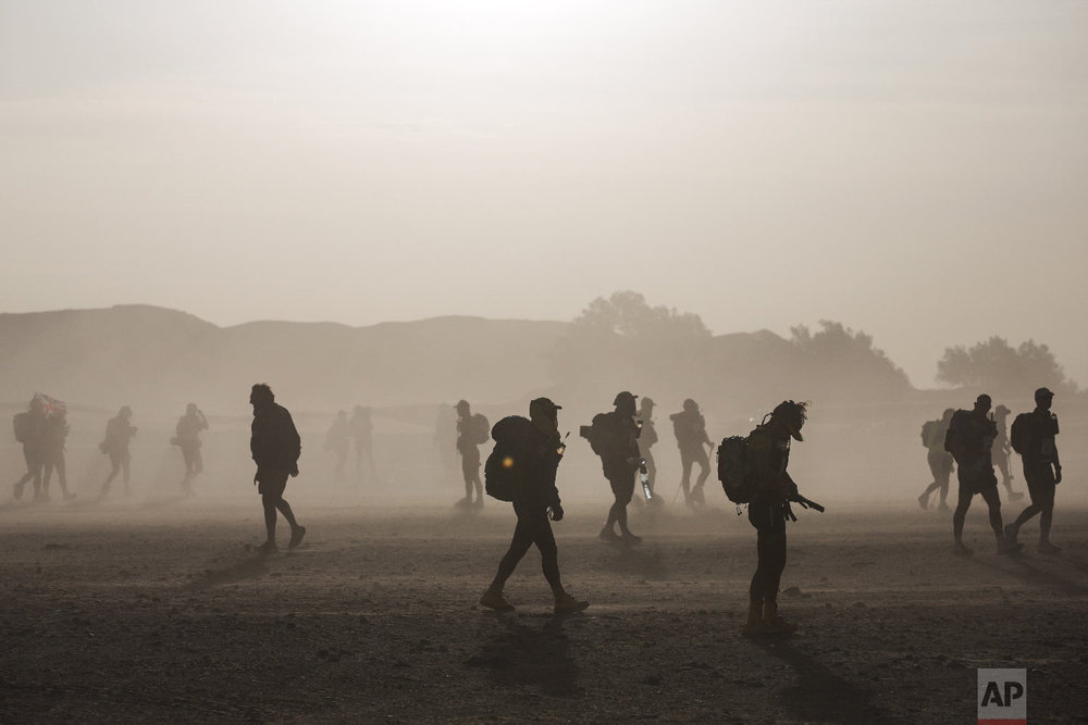 Competitors walk during a sandstorm at the start of a new stage in the 33rd edition of Marathon des Sables, in the Sahara desert, near Merzouga, southern Morocco, Friday, April 13, 2018. (AP Photo/Mosa'ab Elshamy)