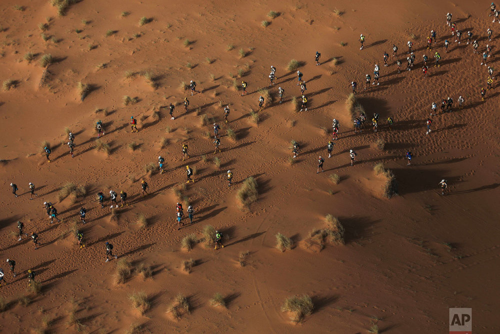 Competitors cross sand dunes as they take part in in the 33rd edition of Marathon des Sables, in the Sahara desert, near Merzouga, southern Morocco, Friday, April 13, 2018. (AP Photo/Mosa'ab Elshamy)