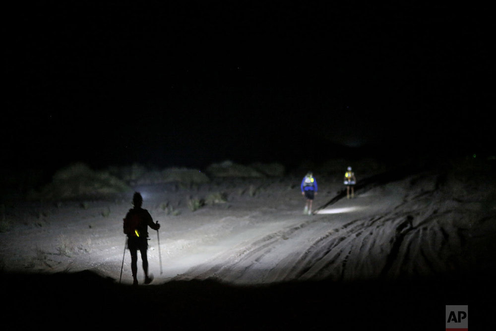 Competitors walk at night as they take part in stage 4 of the 33rd edition of Marathon des Sables, in the Sahara desert, near Merzouga, southern Morocco, Thursday, April 12, 2018. (AP Photo/Mosa'ab Elshamy)