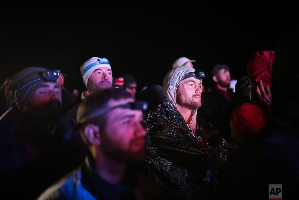 Competitors watch the award ceremony as winners of the 33rd edition of Marathon des Sables receive their awards, in the Sahara desert, near Merzouga, southern Morocco, Friday, April 13, 2018. (AP Photo/Mosa'ab Elshamy)