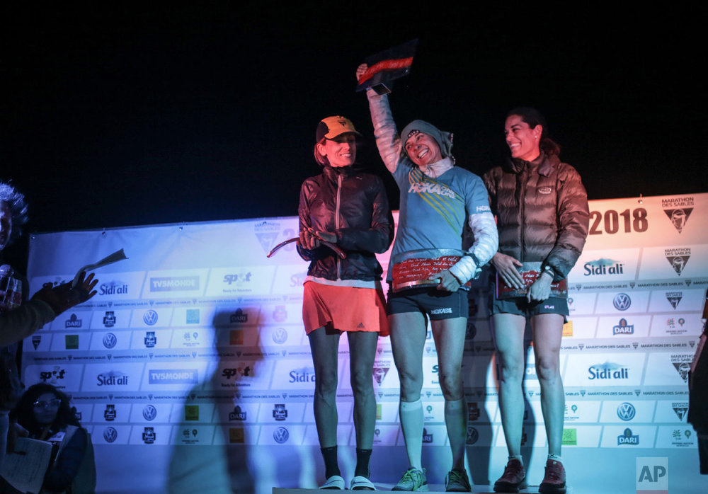 The female winners of the the 33rd edition of Marathon des Sables,Magdalena Boulet, center, Bouchra Eriksen, left, and Gemma Game, right, react as they receive their awards, in the Sahara desert, near Merzouga, southern Morocco, Friday, April 13, 2018. (AP Photo/Mosa'ab Elshamy)