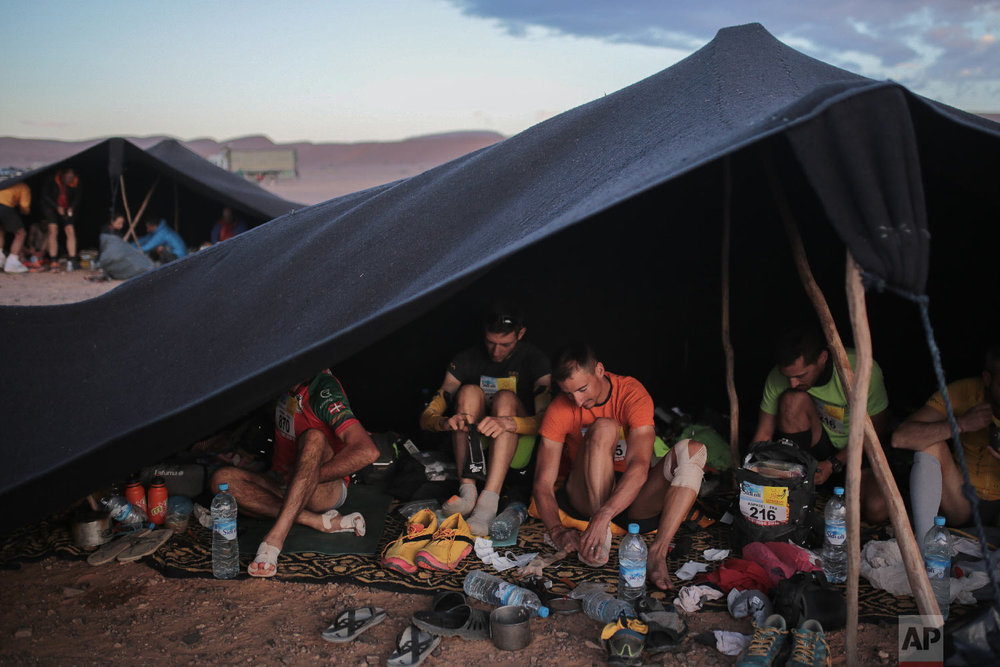 Competitors prepare in the bivouac before sunrise as they take part in the 33rd edition of Marathon des Sables, in the Sahara desert, near Merzouga, southern Morocco, Friday, April 13, 2018. (AP Photo/Mosa'ab Elshamy)
