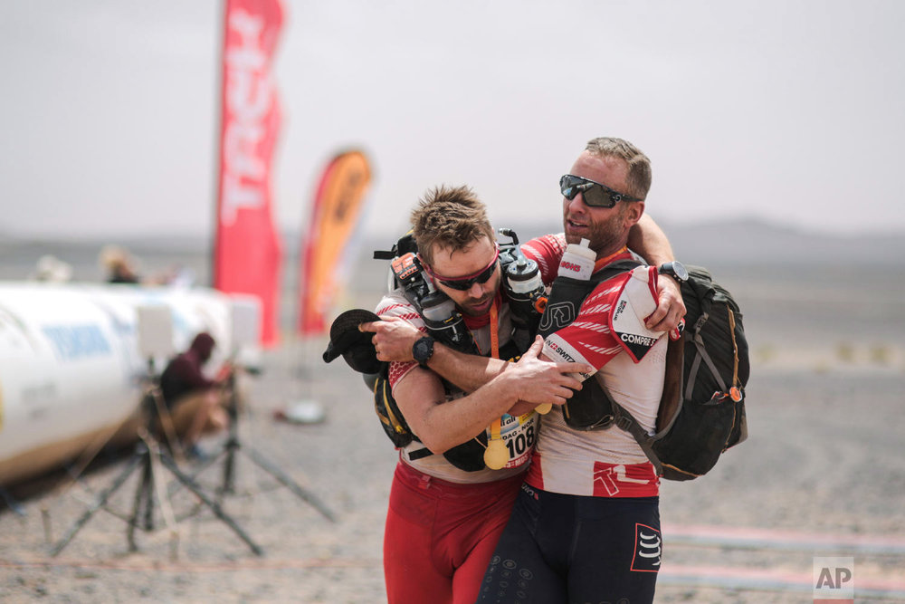 A competitor helps his teammate as they cross the finish line of the 33rd edition of Marathon des Sables, in the Sahara desert, near Merzouga, southern Morocco, Friday, April 13, 2018. (AP Photo/Mosa'ab Elshamy)