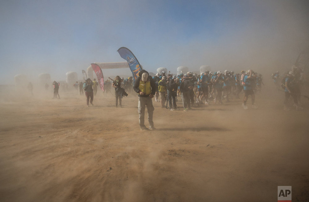A sandstorm sweeps across as competitors take part in the 33rd edition of Marathon des Sables, in the Sahara desert, near Merzouga, southern Morocco, Saturday, April 14, 2018. (AP Photo/Mosa'ab Elshamy)