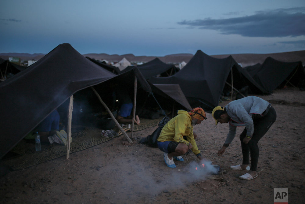 Competitors light a fire before sunrise as they prepare to take part in the 33rd edition of Marathon des Sables, in the Sahara desert, near Merzouga, southern Morocco, Friday, April 13, 2018. (AP Photo/Mosa'ab Elshamy)