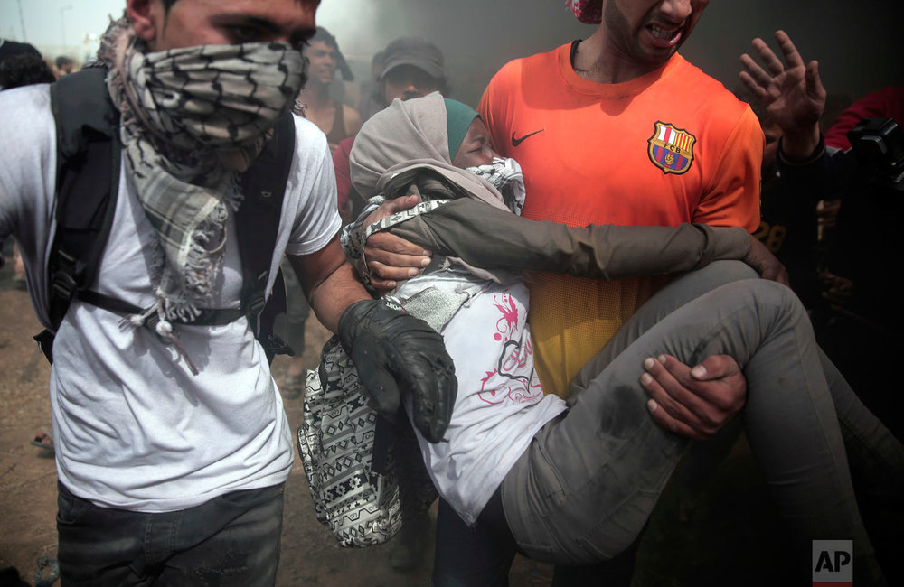 Palestinian protesters evacuate a wounded woman during a protest at the Gaza Strip's border with Israel, Friday, April 20, 2018. Thousands of Palestinians joined the fourth weekly protest on Gaza's border with Israel on Fridays. Hamas says the protests are aimed at breaking a crippling border blockade that was imposed by Israel and Egypt after the Islamic militant group overran Gaza in 2007, a year after winning Palestinian parliament elections. (AP Photo/ Khalil Hamra)