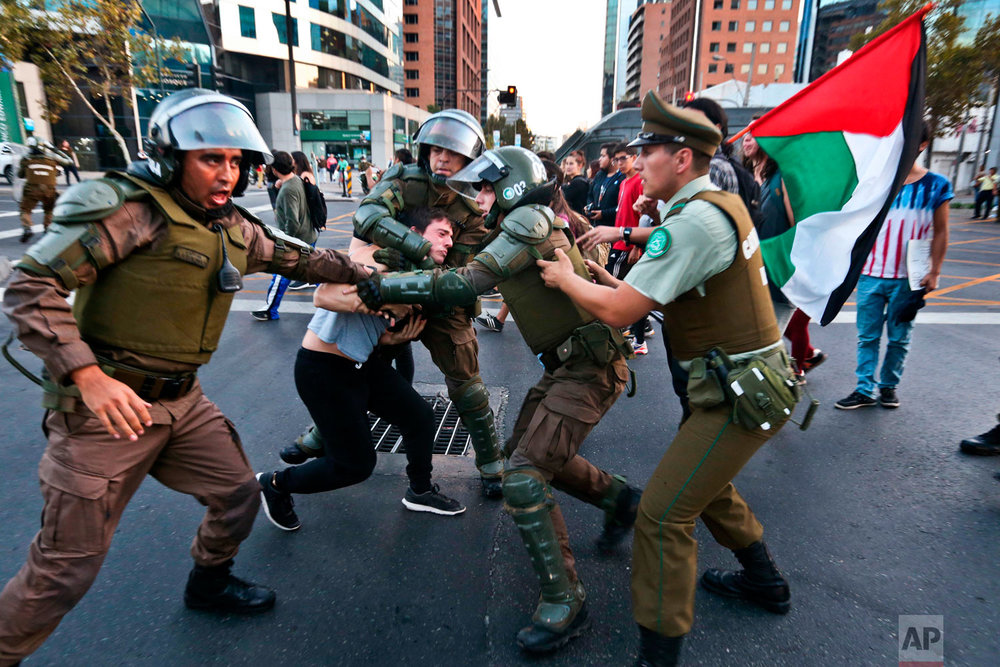 A protester is detained by riot police during a demonstration outside the U.S. embassy in Santiago, Chile, Saturday, April 14, 2018. Supporters of the Chilean Communist party and students took part in an anti-war rally opposing the military strikes in Syria. (AP Photo/Esteban Felix)