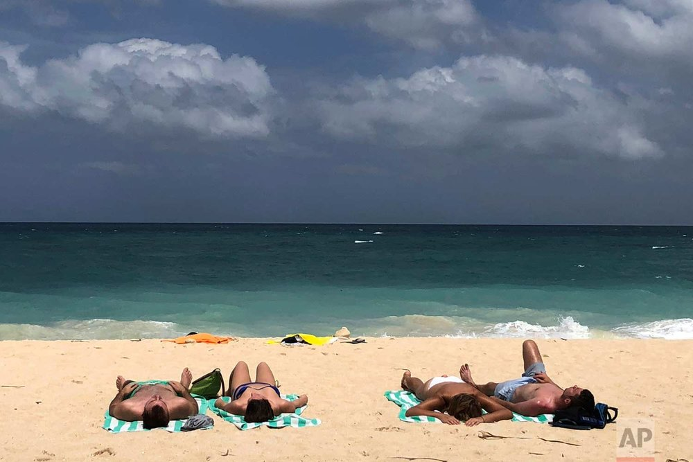 In this March 12, 2018, photo, foreign tourists sunbathe at a beach on Boracay island, central Aklan province, Philippines. (AP Photo/Aaron Favila)