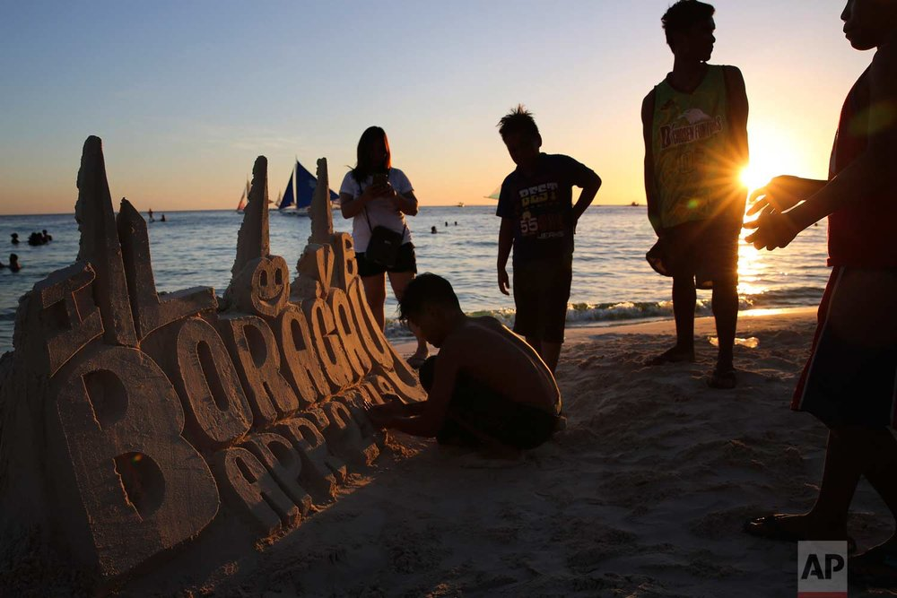 Boys sculpt a sign with sand at the country's most famous beach resort island of Boracay, in central Aklan province, Philippines on Tuesday, April 24, 2018.  (AP Photo/Aaron Favila)