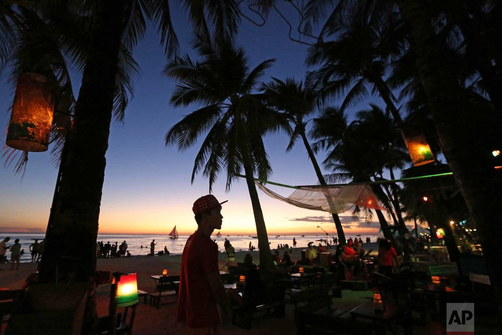 A waiter stands outside their restaurant as the sun sets at the country's most famous beach resort island of Boracay, in central Aklan province, Philippines on Tuesday, April 24, 2018. (AP Photo/Aaron Favila)