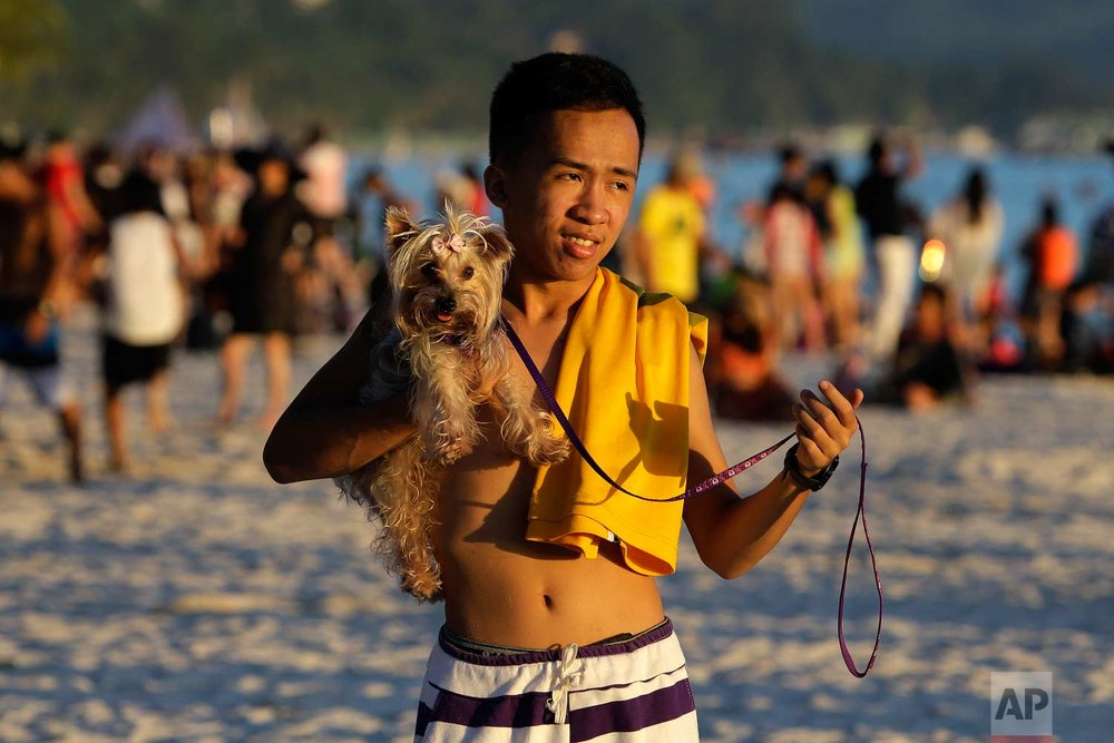A tourist walks with his dog, on the country's most famous beach resort island of Boracay, in central Aklan province, Philippines, Tuesday, April 24, 2018.  (AP Photo/Aaron Favila)