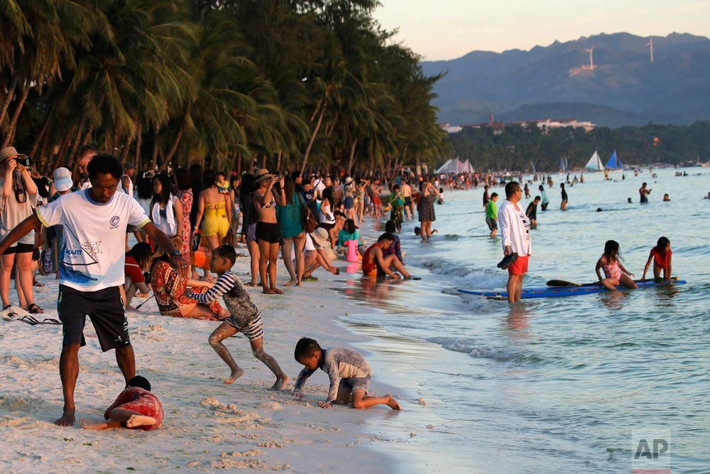 "Tourists crowd the beach front as they wait for the sun set, on the country's most famous beach resort island of Boracay, in central Aklan province, Philippines, Tuesday, April 24, 2018. Thousands of workers will be affected when the resort closes after Philippine President Rodrigo Duterte ordered its closure on April 26 for up to six months after saying the waters off its famed white-sand beaches had become a ""cesspool"" due to overcrowding and development. (AP Photo/Aaron Favila)"