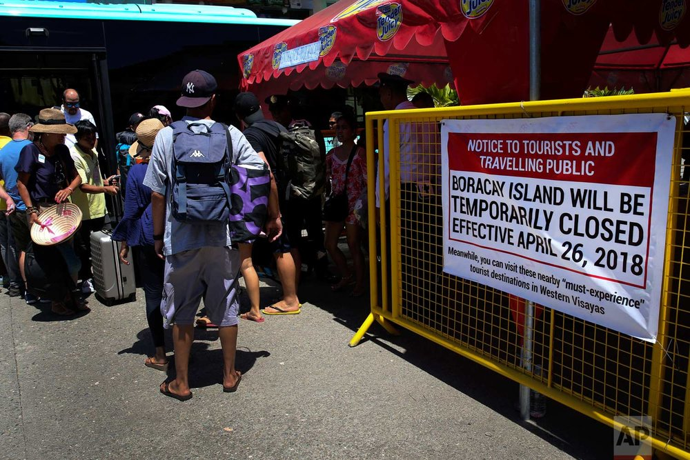 "A sign is placed outside the port in Caticlan, the gateway to the country's most famous beach resort island of Boracay, in central Aklan province, Philippines on Tuesday, April 24, 2018. Thousands of workers will be affected when Boracay will be closed after Philippine President Rodrigo Duterte orders it's closure on April 26 for up to six months after saying the waters off it's famed white-sand beaches had become a ""cesspool"" due to overcrowding and development. (AP Photo/Aaron Favila)"