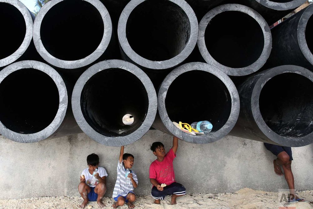 Young residents sit underneath drainage pipes as the government implements the temporary closure of the country's most famous beach resort island of Boracay, in central Aklan province, Philippines, on Thursday, April 26, 2018. Boracay, famed for it's white-sand beaches, closes for up to six months to recover from overcrowding and development. (AP Photo/Aaron Favila)