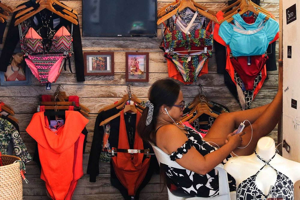 "A woman who sells swimwear waits for customers at the country's most famous beach resort island of Boracay, in central Aklan province, Philippines on Tuesday, April 24, 2018. Thousands of workers will be affected when Boracay will be closed after Philippine President Rodrigo Duterte orders it's closure on April 26 for up to six months after saying the waters off it's famed white-sand beaches had become a ""cesspool"" due to overcrowding and development. (AP Photo/Aaron Favila)"
