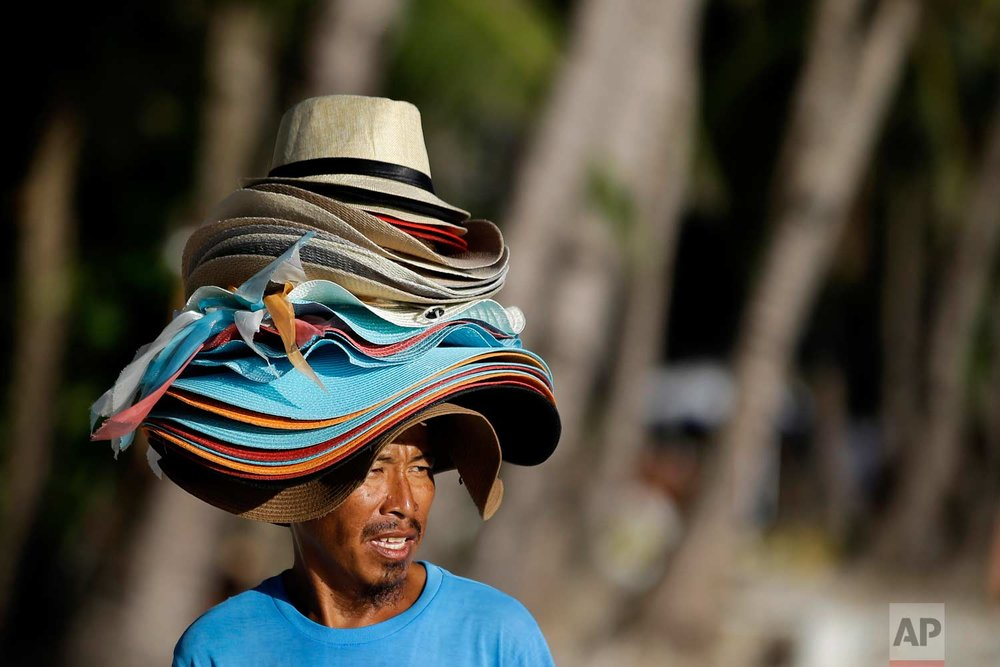 "A hat vendor walks along the sea front of the country's most famous beach resort island of Boracay, in central Aklan province, Philippines, Tuesday, April 24, 2018. Thousands of workers will be affected when the island closes after Philippine President Rodrigo Duterte ordered its closure on April 26 for up to six months after saying the waters off its famed white-sand beaches had become a ""cesspool"" due to overcrowding and development. (AP Photo/Aaron Favila)"