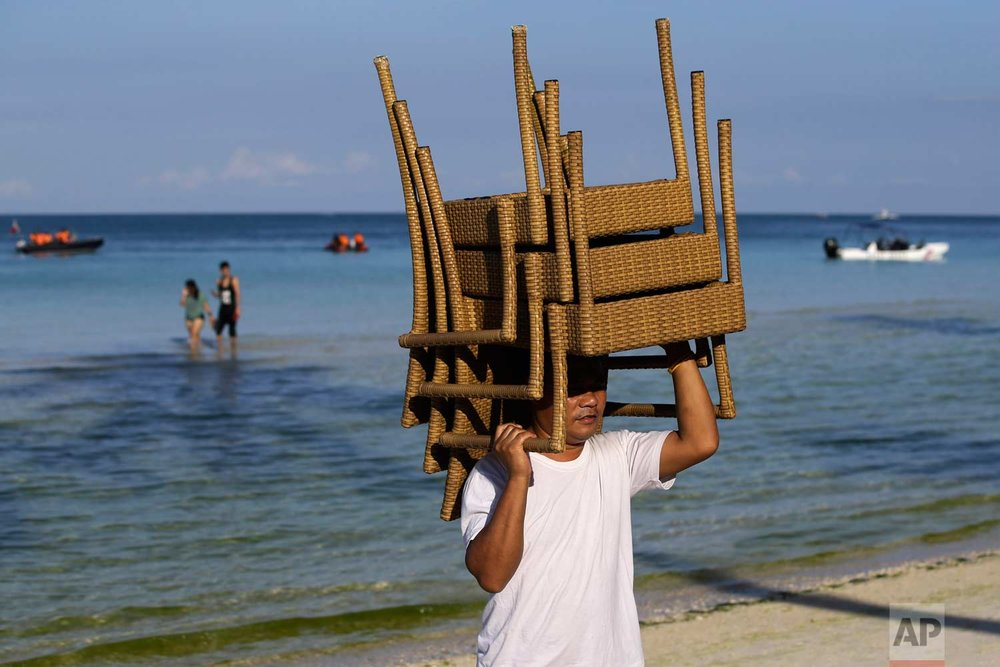 "A man carries chairs at the country's most famous beach resort island of Boracay, in central Aklan province, Philippines Wednesday, April 25, 2018, a day before the government implements its temporary closure. Thousands of workers will be affected when Boracay will be closed after Philippine President Rodrigo Duterte orders its closure on April 26 for up to six months after saying the waters off its famed white-sand beaches had become a ""cesspool"" due to overcrowding and development. (AP Photo/Aaron Favila)"