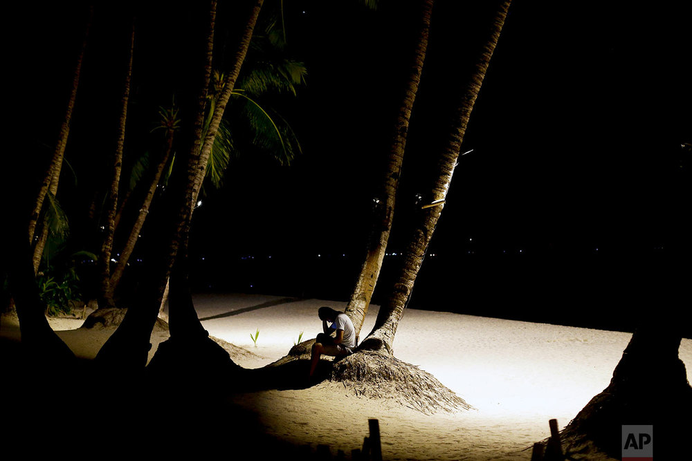 A man sits under a tree as many of the beachfront restaurants and business establishments stopped operations today as the government implements the temporary closure of the country's most famous beach resort island of Boracay, in central Aklan province, Philippines, on Thursday, April 26, 2018. Many workers on the island were left jobless as Boracay, famed for it's powdery white-sand beaches, closes for up to six months to recover from overcrowding and development. (AP Photo/Aaron Favila)