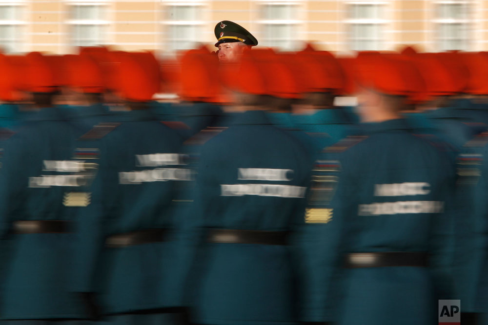 A commander rides a car past troops greeting them during a rehearsal for the Victory Day military parade which will take place at Dvortsovaya (Palace) Square on May 9 to celebrate 73 years after the victory in WWII, in St.Petersburg, Russia, Thursday, April 26, 2018. (AP Photo/Dmitri Lovetsky)