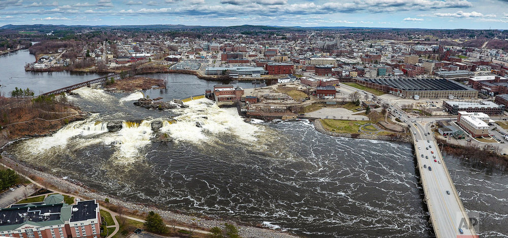 In this aerial photo, Great Falls on the Androscoggin River between Lewiston, rear, and Auburn, Maine, overflows with spring runoff and recent rainfall Friday April 27, 2018. (Russ Dillingham/Sun Journal via AP)
