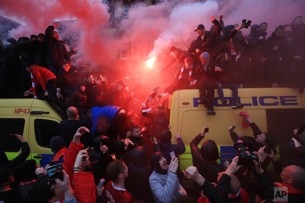 Soccer fans light flares and clamber atop Police vans before their Champions League, Semi Final First Leg soccer match at Anfield in Liverpool, England, Tuesday April 24, 2018. (Peter Byrne/PA via AP)