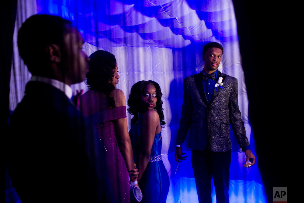 """Swartz Creek seniors Yasminae Holmes, second from left, and Jada Hall pose for a photo booth camera as their dates Anthony Roberts, left, a Swartz Creek senior, and Chris Long, a Beecher senior, watch while attending the Swartz Creek High School prom with a """"By the Light of the Moon"""" theme, on Saturday, April 21, 2018, in Owosso, Mich. (Jake May/The Flint Journal-MLive.com via AP)"""
