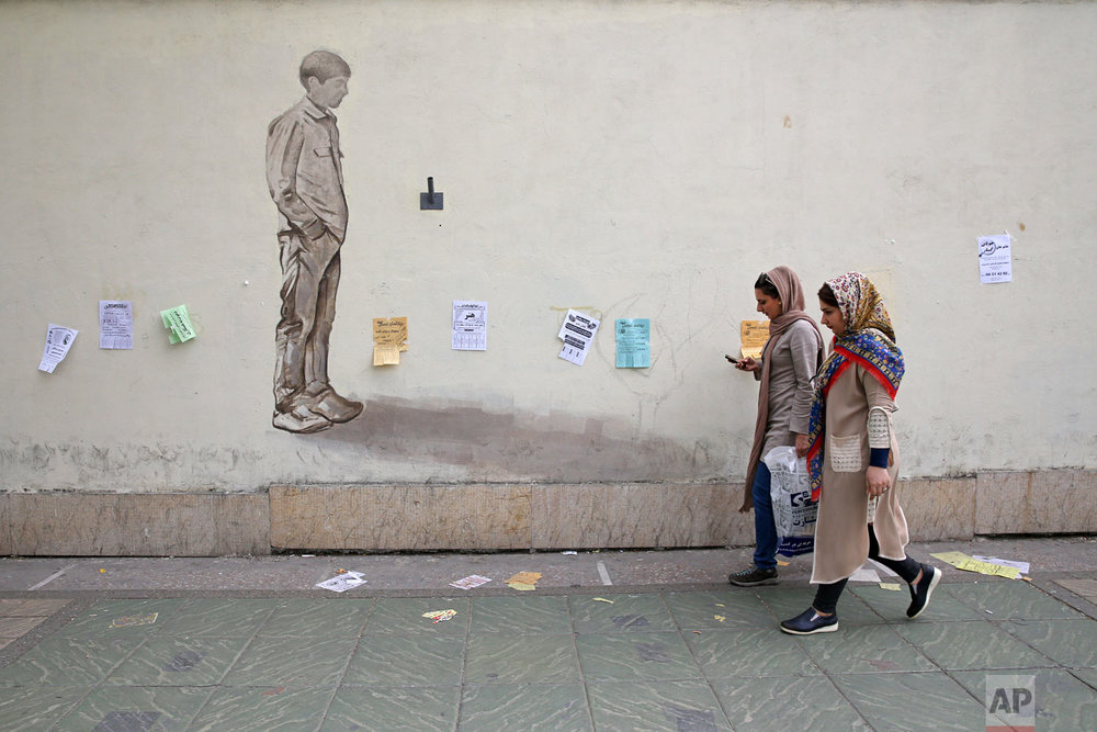 In this Sunday, April 22, 2018, photo, women make their way on a sidewalk in downtown Tehran, Iran. A grainy video of female officers from Iran's morality police assaulting a young woman whose headscarf only loosely covered her hair has sparked a new public debate on the decades-long requirement for women in the Islamic Republic. (AP Photo/Vahid Salemi)