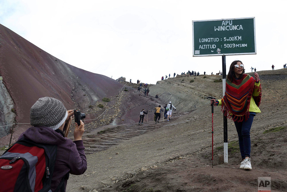 In this March 2, 2018 photo, a tourist poses for a photo at the entrance that leads to Rainbow Mountain, in Pitumarca, Peru. (AP Photo/Martin Mejia)