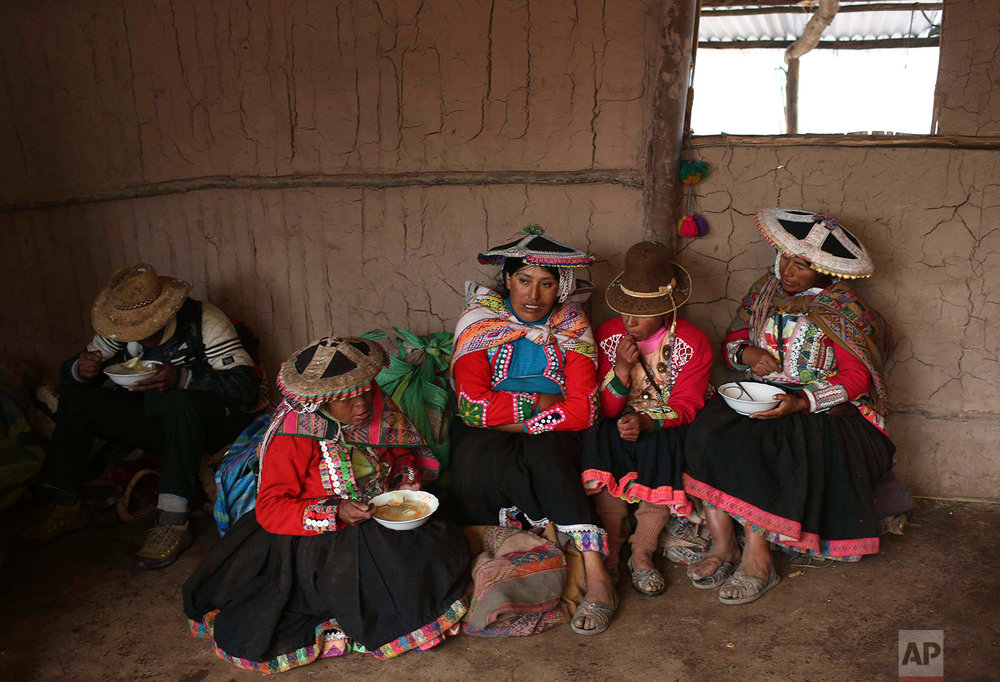 In this April 5, 2018 photo, a group of Andean muleteers break for lunch during a tour guide to Rainbow Mountain, in Pitumarca, Peru. (AP Photo/Martin Mejia)