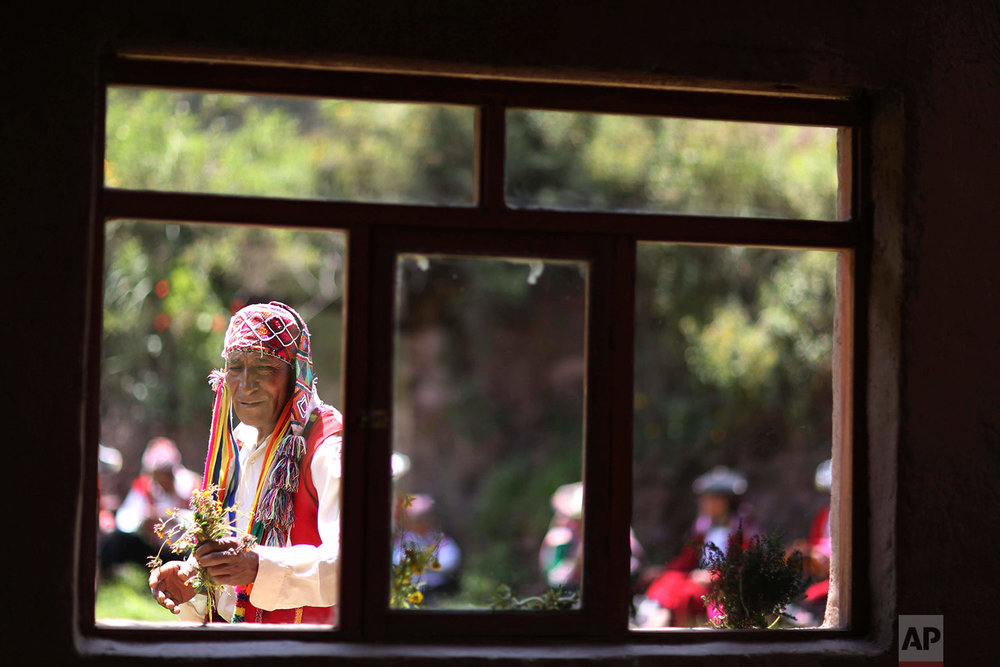In this April 4, 2018 photo, a farmer who now sells Andean clothes, collects flowers while he waits for tourists who have come to see Rainbow Mountain, in Pitumarca, Peru. (AP Photo/Martin Mejia)