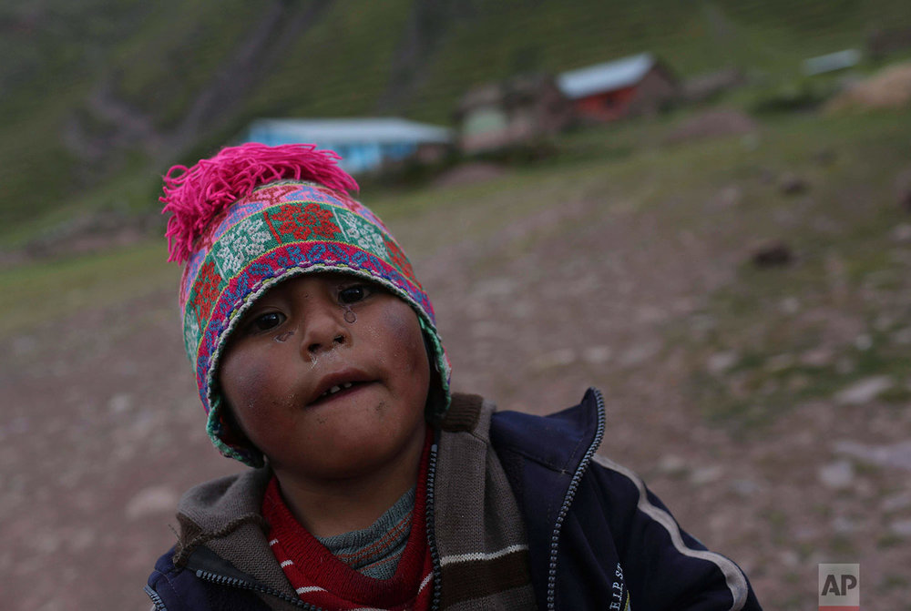 In this April 4, 2018 photo, Henry, 5-years-old, eyes the camera outside his school in Pitumarca, Peru, near Rainbow Mountain. (AP Photo/Martin Mejia)