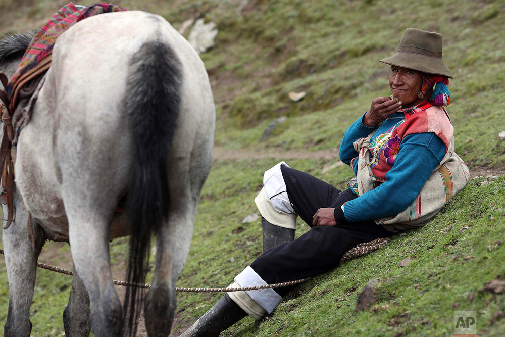 In this March 2, 2018 photo, an Andean muleteer rests during a break from guiding tourists to Rainbow Mountain, in Pitumarca, Peru. (AP Photo/Martin Mejia)