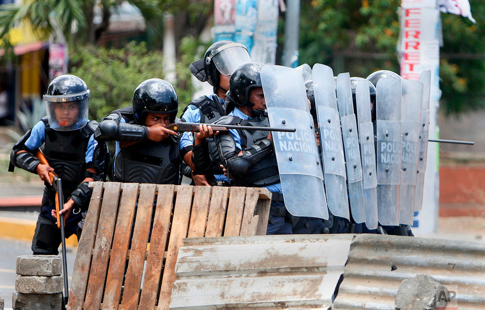 In this April 20, 2018 photo, a Nicaraguan police officer aims his weapon at protesting students during a third day of violent clashes in Managua, Nicaragua. The clashes, pitting protesters opposed to social security reforms against riot police and pro-government groups, have rocked the capital, and a half-dozen other cities, killing 63 people according to a non-governmental rights group. (AP Photo/Alfredo Zuniga)