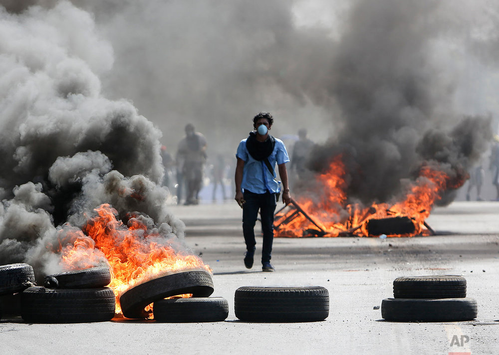 A masked protester walks between burning barricades in Managua, Nicaragua, Friday, April 20, 2018. The clashes, pitting protesters opposed to social security reforms against riot police and pro-government groups, have rocked the capital, and a half-dozen other cities over the last three days. The Organization of American States have expressed concern over the heavy-handed crackdown, while also calling on demonstrators to protest peacefully. (AP Photo/Alfredo Zuniga)