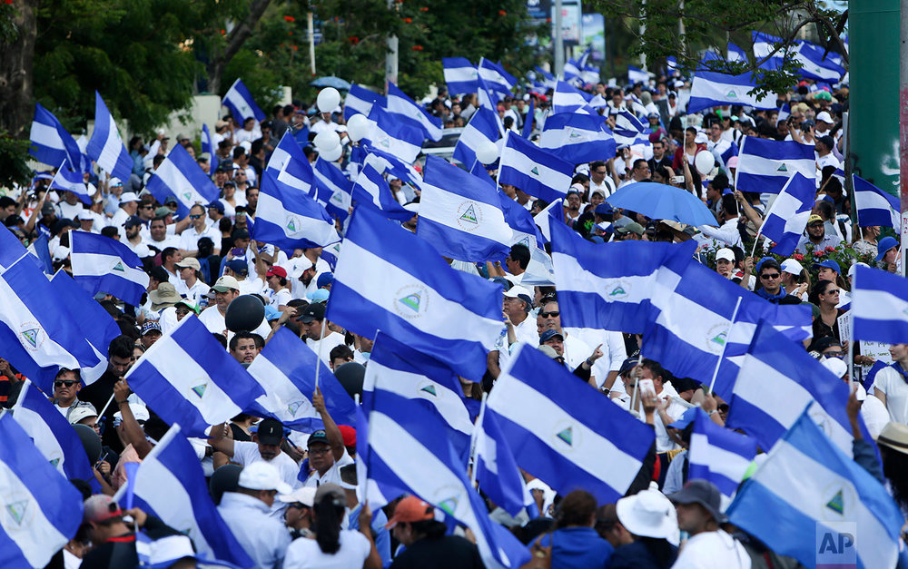 Demonstrators protesting government repression wave Nicaraguan flags in Managua, Nicaragua, Monday, April 23, 2018. People also marched to call for peace after several days of violent demonstrations set off by a social security overhaul. (AP Photo/Alfredo Zuniga)