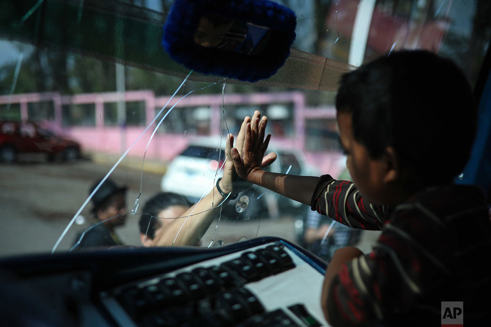 "A boy says goodbye to a friend through the windshield of a bus that will carry him to Mexico City from the sports club where Central American migrants traveling with the annual ""Stations of the Cross"" caravan had been camping out in Matias Romero, Oaxaca State, Mexico, Thursday, April 5, 2018. Migrants in the caravan that drew criticism from U.S. President Donald Trump began packing up their meager possessions and boarding buses to the Mexican capital and the nearby city of Puebla. (AP Photo/Felix Marquez)"