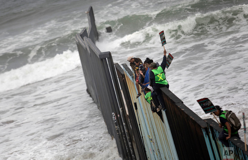 Central American migrants traveling with a caravan sit momentarily on top of the border wall during a gathering of migrants living on both sides of the border, on the beach where the border wall ends in the ocean, with Tijuana, Mexico at left and San Diego at right, Sunday, April 29, 2018. U.S. immigration lawyers are telling Central Americans in a caravan of asylum-seekers that traveled through Mexico to the border with San Diego that they face possible separation from their children and detention for many months. They say they want to prepare them for the worst possible outcome. (AP Photo/Hans-Maximo Musielik)