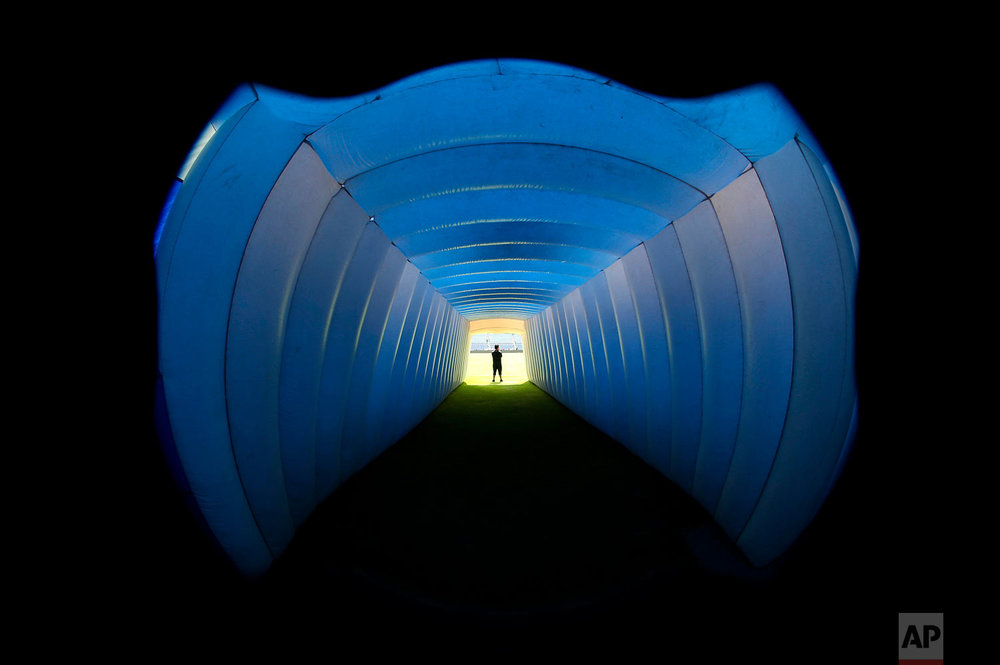 An inflatable tunnel is illuminated blue before Cruz Azul players go to the field for their Mexico league soccer match with Morelia, at Cruz Azul Stadium in Mexico City, April 21, 2018. This is the last match Cruz Azul will play at their home stadium, inaugurated in 1946, before it is demolished to make way for a shopping center. (AP Photo/Marco Ugarte)