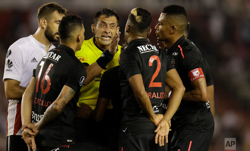 Chilean referee Luis Bascunan talks to Colombia's Independiente Santa Fe players during a Copa Libertadores soccer match against Argentina's River Plate in Buenos Aires, Argentina, Thursday, April 5, 2018. (AP Photo/Natacha Pisarenko)