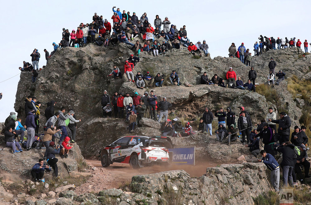 People watch driver Ott Tanak and his co driver Martin Jarveoja, both from Estonia, race their Toyota Yaris WRC during the FIA World Rally Championship in El Condor, Cordoba, Argentina, Sunday, April 29, 2018. (AP Photo/Nicolas Aguilera)