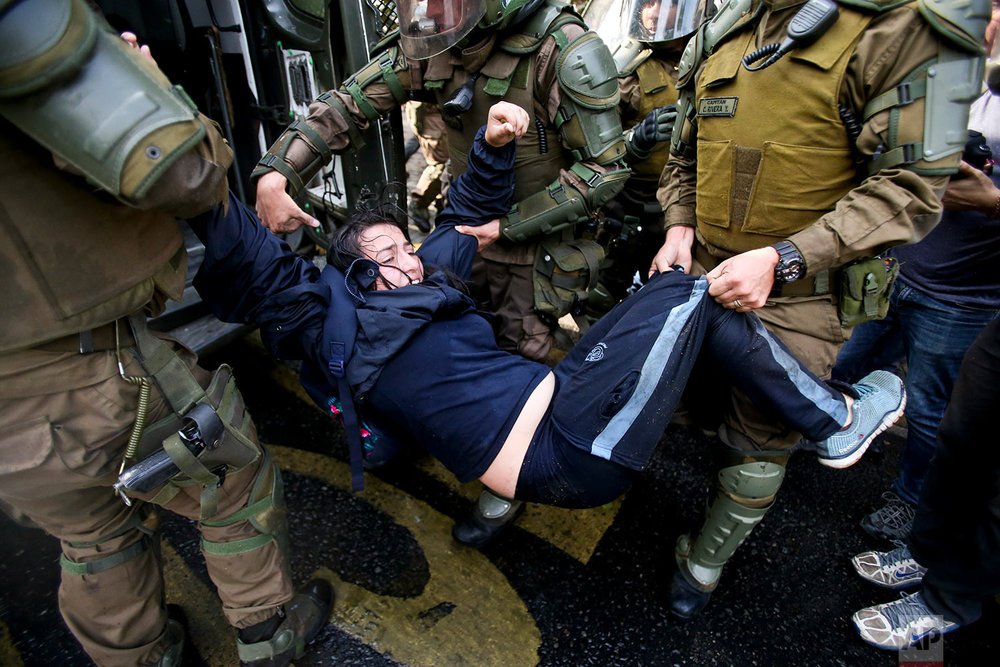 Police detain a student demonstrator during a protest demanding education reform, including free access to school for all ages, from president Sebastian Pinera's government, in Santiago, Chile, Thursday, April 5, 2018. (AP Photo/Esteban Felix)