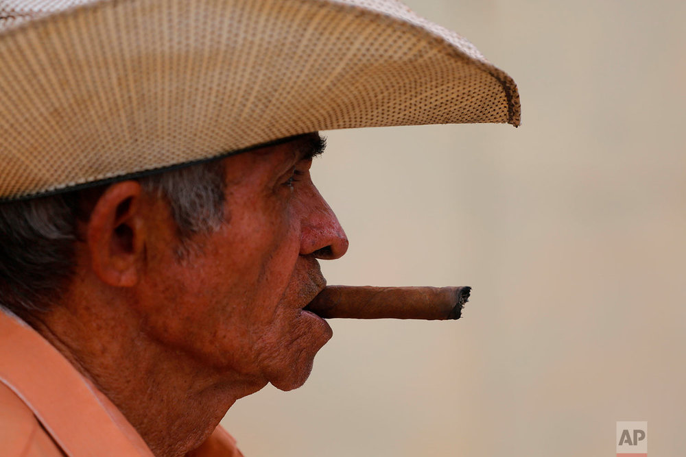 Edelio Jimenez Santana, 81, smokes a cigar in the Vigia neighborhood of Santa Clara, Cuba, where he was a neighbor of Miguel Mario Diaz-Canel Bermudez, the he man who is expected to be Cuba's next president, April 1, 2018. Diaz-Canel was born and raised in Santa Clara where he spent nine years in a role akin to a governor. (AP Photo/Desmond Boylan)