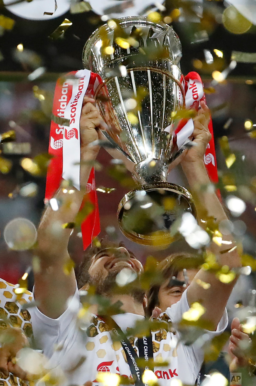 Chivas' Jair Pereira holds the trophy aloft as he celebrates his team's victory over Toronto FC in the CONCACAF Champions League final soccer match, in Guadalajara, Mexico, Wednesday, April 25, 2018. Chivas defeated Toronto FC in a penalty shoot out. (AP Photo/Eduardo Verdugo)