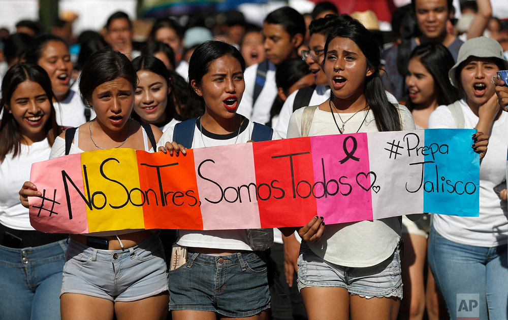 "Students hold a sign that reads in Spanish ""It's not three, it's all of us"" during a protest against the murder of three film students who have become emblematic of Mexico's missing, in Guadalajara, Mexico, Thursday, April 26, 2018. Prosecutors said the three were abducted by the Jalisco New Generation Cartel because they were filming a school project at a house used by the rival Nueva Plaza gang. The students were using the residence because it belonged to one of their aunts. (AP Photo/Eduardo Verdugo)"