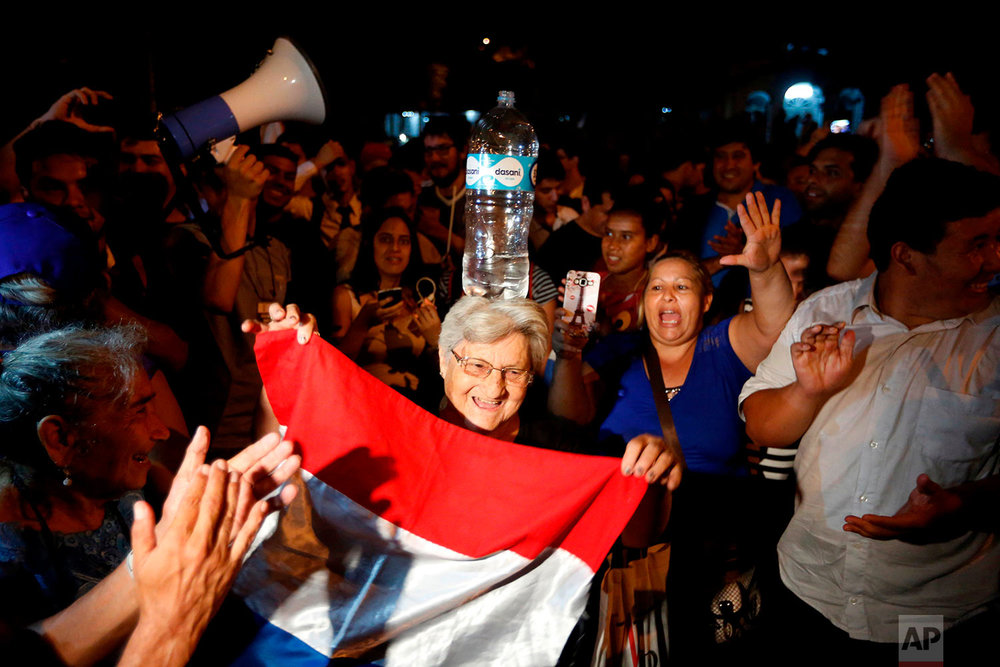 In this April 24, 2018 photo, a woman balances a bottle of water on her head as she performs a traditional dance during a gathering by supporters of presidential candidate Efrain Alegre, who lost the election, to protest what they believe was electoral fraud in recent general elections, outside the Superior Tribunal of Electoral Justice, a court that manages election cases, in Asuncion, Paraguay. Alegre declined to concede, saying he would wait for the final count, though electoral officials said there were not enough ballots left to be counted to change the result. The new president, Mario Abdo Benitez of the governing Colorado Party, begins a five-year term Aug. 15. (AP Photo/Jorge Saenz)
