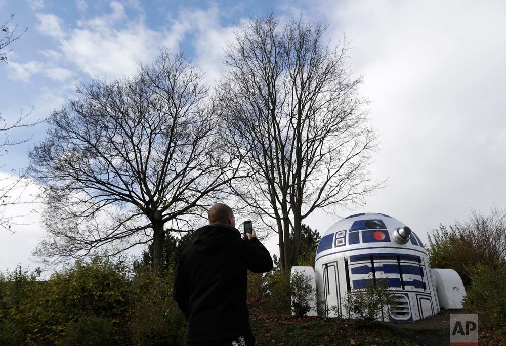 """A man takes a photo of an air ventilation turned by an unknown street artist into Star Wars'  R2-D2  in a park in Prague, Czech Republic, Saturday, Oct. 28, 2017. According to Prague 2 district mayor, Jana Cernochova, the robot is there to stay. """"We do not support illegal graffiti, of course, but we like the decor on this unsightly shaft,"""" she said to local media. (AP Photo/Petr David Josek)"""
