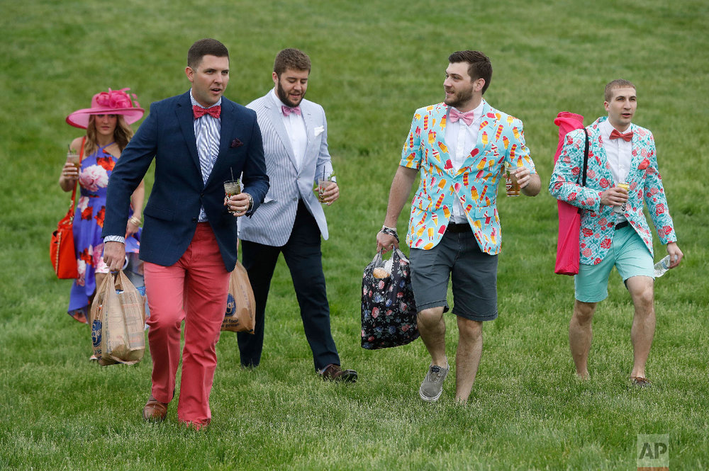 Fans walk in the infield before the 144th running of the Kentucky Derby horse race at Churchill Downs Saturday, May 5, 2018, in Louisville, Ky. (AP Photo/John Minchillo)