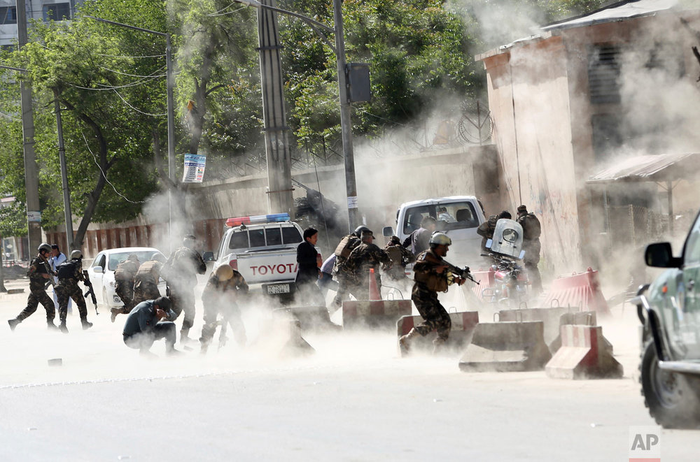 Security forces run from the site of a suicide attack after a second bombing in Kabul, Afghanistan, Monday, April 30, 2018. A coordinated double suicide bombing hit central Kabul on Monday morning. Monday marked the deadliest assault on reporters since the fall of the Taliban in 2001, according to Reporters Without Borders, also known by its French acronym RSF. The bombings in Kabul killed 25 people and wounded at least 45. (AP Photo/Massoud Hossaini)