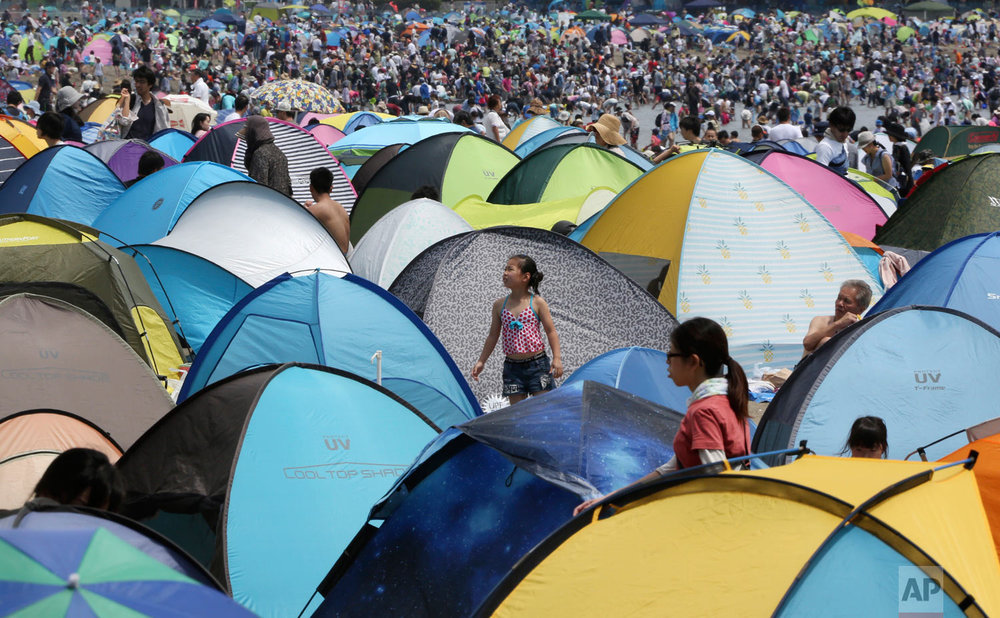 Holiday makers walk past tents on the beach to hunt for clams in Yokohama, near Tokyo, Monday, April 30, 2018. (AP Photo/Koji Sasahara)